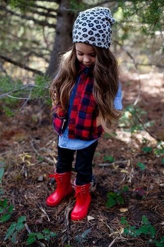 Cómo combinar: chaqueta sin mangas roja, camisa de vestir vaquera azul, leggings negros, botas de lluvia rojas