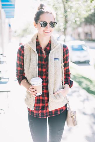 Cómo combinar: chaqueta sin mangas de forro polar en beige, camisa de vestir de tartán en rojo y negro, vaqueros pitillo desgastados negros, bolso bandolera de cuero en beige