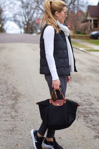 Cómo combinar: chaqueta sin mangas acolchada negra, jersey con cuello circular blanco, leggings en gris oscuro, deportivas negras