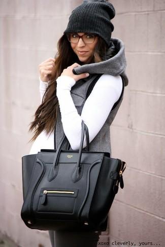 Cómo combinar: chaqueta sin mangas gris, jersey de cuello alto blanco, leggings en gris oscuro, bolsa tote de cuero negra