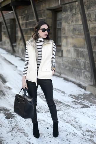 Cómo combinar: chaqueta sin mangas blanca, jersey de cuello alto de rayas horizontales en blanco y negro, pantalones pitillo de cuero negros, botines de ante negros