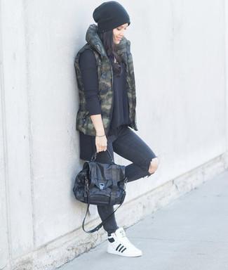 Cómo combinar: chaqueta sin mangas de camuflaje verde oscuro, jersey oversized negro, vaqueros pitillo desgastados en gris oscuro, zapatillas altas de cuero blancas