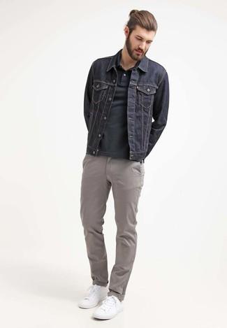 Cómo combinar: chaqueta vaquera azul marino, camisa polo negra, pantalón chino gris, tenis blancos