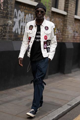 Cómo combinar: chaqueta vaquera bordada blanca, camiseta con cuello circular estampada en negro y blanco, pantalón chino azul marino, tenis de lona negros