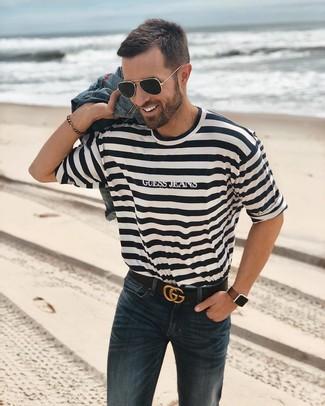 Cómo combinar: chaqueta vaquera azul, camiseta con cuello circular de rayas horizontales en blanco y negro, vaqueros azul marino, correa de cuero negra