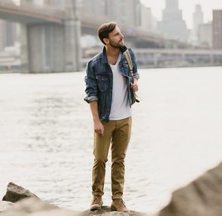 Cómo combinar: chaqueta vaquera azul marino, camiseta con cuello en v blanca, pantalón chino mostaza, botas safari de ante marrónes