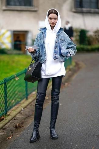 Cómo combinar: chaqueta vaquera azul, sudadera con capucha blanca, leggings de cuero negros, botas sobre la rodilla de cuero negras