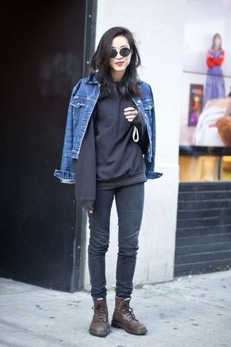 Cómo combinar: chaqueta vaquera azul, sudadera negra, vaqueros pitillo en gris oscuro, botas planas con cordones de cuero en marrón oscuro