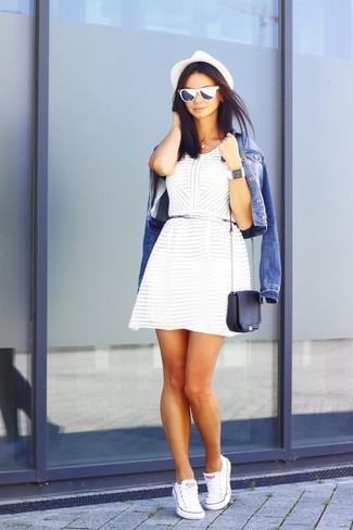 Cómo combinar: chaqueta vaquera azul, vestido skater blanco, tenis de lona blancos, bolso bandolera de cuero negro