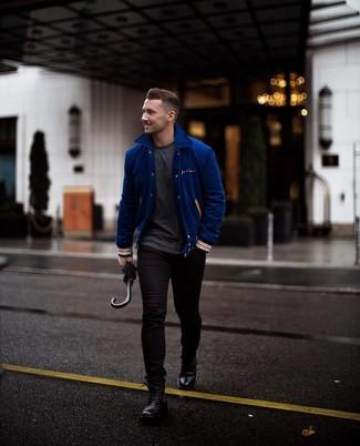 Cómo combinar: chaqueta varsity azul, camiseta con cuello circular en gris oscuro, vaqueros pitillo negros, botas casual de cuero negras