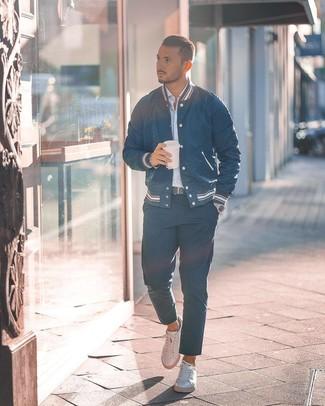 Cómo combinar: chaqueta varsity azul marino, camisa de manga larga de rayas verticales celeste, pantalón chino azul marino, tenis de cuero blancos