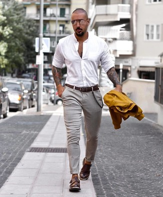 Cómo combinar: chaqueta varsity mostaza, camisa de manga larga blanca, pantalón chino gris, zapatos con doble hebilla de cuero en marrón oscuro
