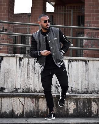 Cómo combinar: chaqueta varsity en gris oscuro, camiseta con cuello circular negra, pantalón de chándal negro, tenis de cuero en negro y blanco