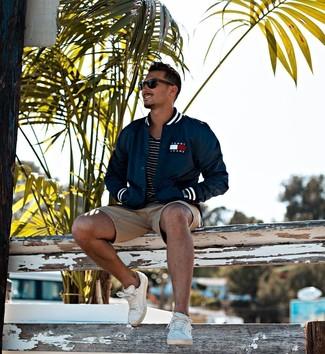 Cómo combinar: chaqueta varsity azul marino, camiseta con cuello circular de rayas horizontales en negro y blanco, pantalones cortos marrón claro, tenis de cuero blancos
