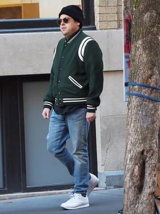 Cómo combinar: chaqueta varsity verde oscuro, camiseta con cuello circular negra, vaqueros celestes, deportivas blancas