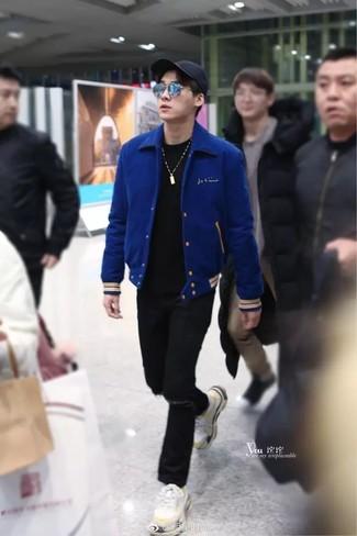 Cómo combinar: chaqueta varsity azul, camiseta con cuello circular negra, vaqueros desgastados negros, deportivas blancas