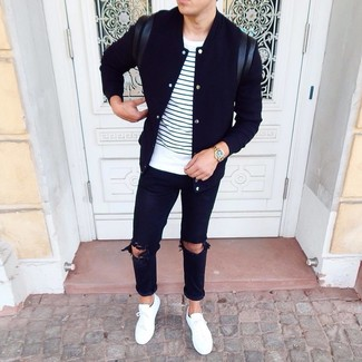 Cómo combinar: chaqueta varsity negra, camiseta con cuello circular de rayas horizontales en blanco y azul marino, vaqueros desgastados negros, tenis blancos