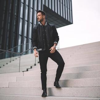 Cómo combinar: chaqueta varsity en negro y blanco, camiseta con cuello circular negra, vaqueros pitillo negros, botines chelsea de cuero negros