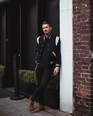 Cómo combinar: chaqueta varsity en negro y blanco, camiseta con cuello circular negra, vaqueros pitillo negros, botines chelsea de ante marrónes