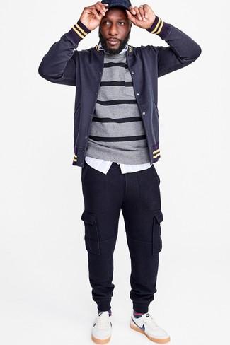 Cómo combinar: chaqueta varsity azul marino, jersey con cuello circular de rayas horizontales gris, camisa de manga larga de rayas verticales celeste, pantalón de chándal azul marino