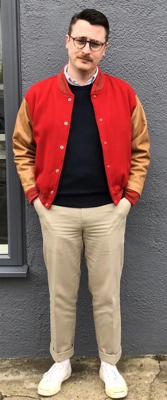 Cómo combinar: chaqueta varsity roja, jersey con cuello circular negro, camisa de manga larga blanca, pantalón chino en beige