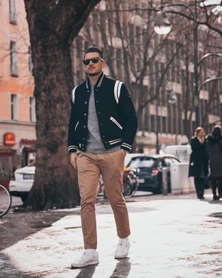 Cómo combinar: chaqueta varsity en negro y blanco, jersey con cuello circular gris, pantalón chino marrón claro, tenis blancos