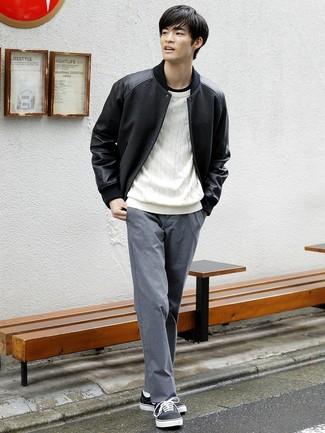Cómo combinar: chaqueta varsity negra, jersey de ochos blanco, camiseta con cuello circular negra, pantalón chino gris