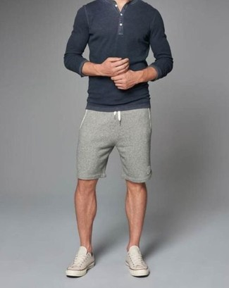 A dark grey henley shirt and grey shorts are great staples that will integrate perfectly within your current looks. A pair of beige low top sneakers will seamlessly integrate within a variety of outfits.