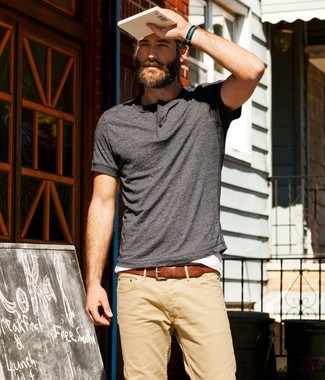 A dark grey henley shirt with tan chinos has become an essential combination for many style-conscious men.
