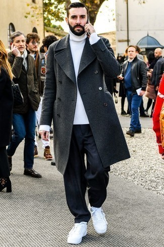 How to Wear Navy Jeans For Men: You'll be surprised at how very easy it is for any man to throw together this effortlessly neat outfit. Just a charcoal overcoat and navy jeans. A trendy pair of white leather low top sneakers is the most effective way to inject a touch of stylish nonchalance into this look.