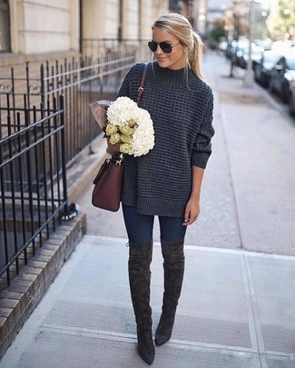 Dress in a dark grey knit oversized sweater and deep blue skinny jeans for a relaxed take on day-to-day wear. Charcoal suede over the knee boots will add a touch of polish to an otherwise low-key look.