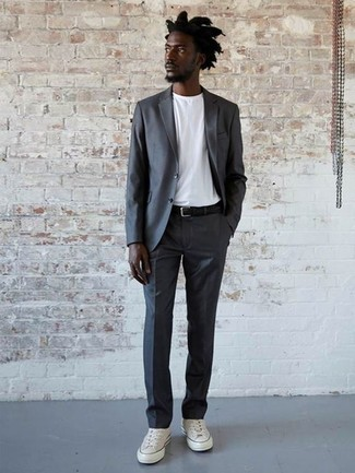 How to Wear a Black Leather Belt For Men: For a cool and casual outfit, opt for a charcoal suit and a black leather belt — these two pieces work wonderfully together. Add a pair of white canvas low top sneakers to this look and the whole outfit will come together brilliantly.