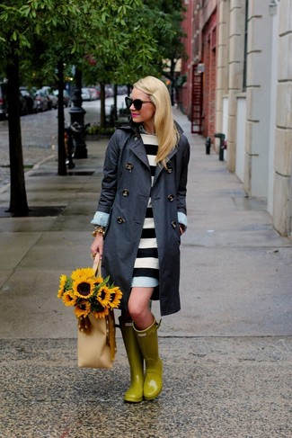 Go for a charcoal trench coat and a white and black striped casual dress for a refined yet off-duty ensemble. Rain boots will contrast beautifully against the rest of the look.