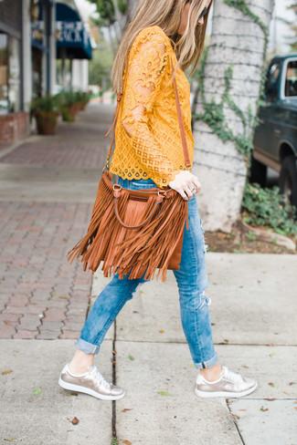 Comment porter: chemisier à manches longues en dentelle jaune, jean skinny déchiré bleu, baskets basses en cuir argentées, sac bandoulière en cuir à franges tabac