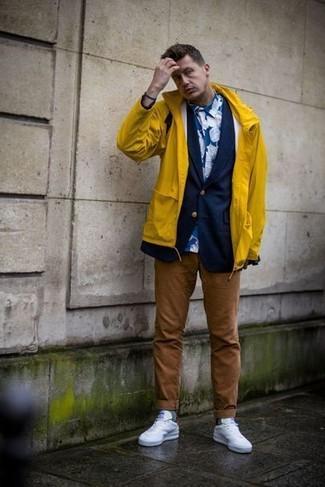 Cómo combinar: chubasquero amarillo, blazer azul marino, camisa de vestir con print de flores azul, pantalón chino marrón