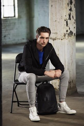 Cómo combinar: chubasquero negro, camiseta con cuello circular azul, pantalón de chándal gris, zapatillas altas de cuero blancas