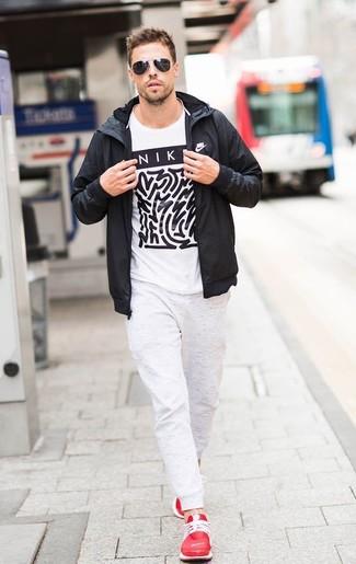 Cómo combinar: chubasquero negro, camiseta con cuello circular estampada en blanco y negro, pantalón de chándal blanco, deportivas rojas