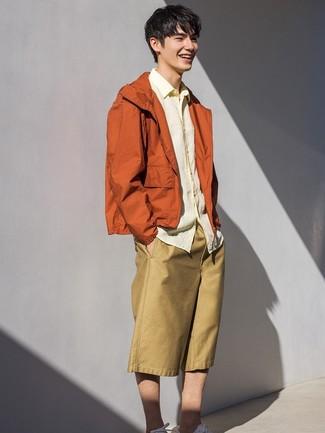 Cómo combinar: chubasquero naranja, camisa de manga larga de lino amarilla, pantalones cortos marrón claro, tenis blancos