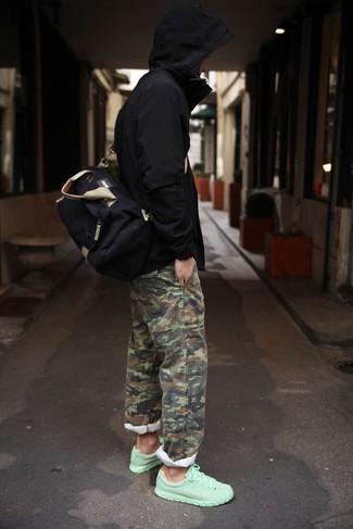 Cómo combinar: chubasquero negro, pantalón chino de camuflaje verde oliva, deportivas en verde menta, bolso baúl de lona negro