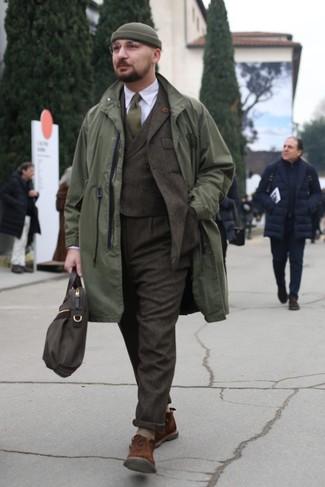 Cómo combinar: chubasquero verde oliva, traje de tres piezas de lana en marrón oscuro, camisa de vestir blanca, botas safari de ante marrónes
