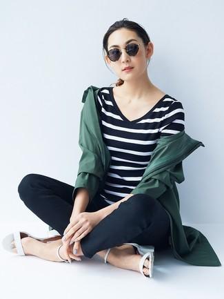 Cómo combinar: chubasquero verde oscuro, camiseta con cuello en v de rayas horizontales en negro y blanco, pantalones pitillo negros, sandalias de tacón de cuero blancas