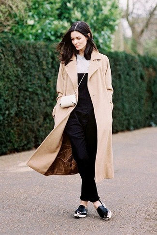 A beige coat and black denim overalls are a great outfit formula to have in your arsenal. Black leather slip-on sneakers will add some edge to an otherwise classic look.