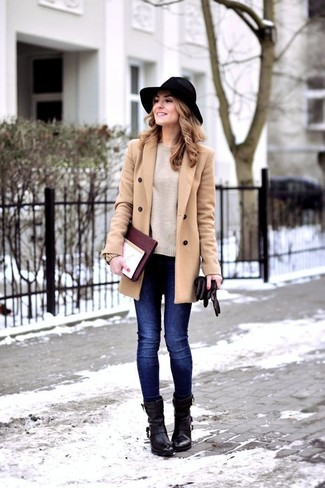 Pairing a nude crew-neck jumper with deep blue skinny jeans is a comfortable option for running errands in the city. Black leather ankle boots are a wonderful choice to complete the look.