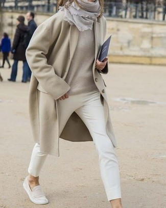 White Canvas Slip-on Sneakers Outfits For Women: A beige coat and white skinny pants are absolute essentials if you're picking out a classic and casual wardrobe that holds to the highest sartorial standards. A pair of white canvas slip-on sneakers will contrast beautifully against the rest of the ensemble.