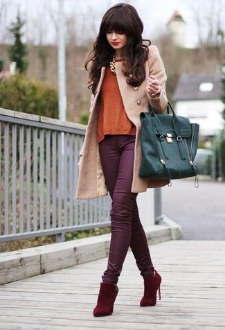 Master the effortlessly chic look in a tan coat and purple jeans. This outfit is complemented perfectly with red suede ankle boots.