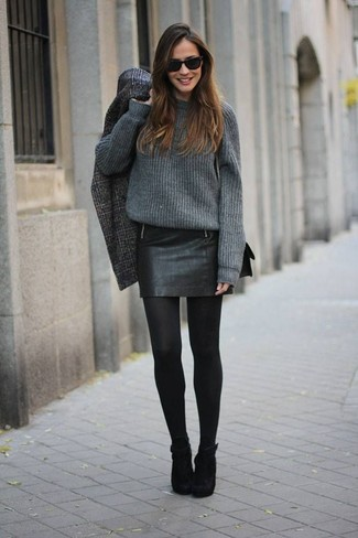 Stand out among other stylish civilians in an oversized sweater and a black leather mini skirt. Take a classic approach with the footwear and choose a pair of black suede ankle boots.