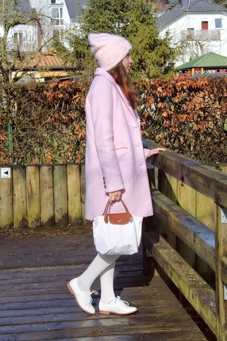 Consider wearing a pink coat for a stylish office ensemble. Round off this look with white leather oxfords.