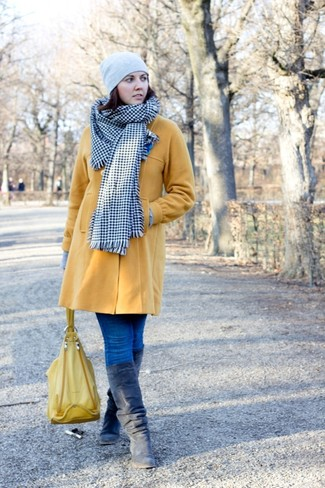 Look stylish yet practical in a mustard coat and blue skinny jeans. Navy suede knee high boots look amazing here. This ensemble can easily become your best asset when braving extreme weather.