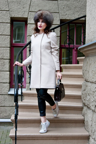 Choose a beige coat and black leather slim jeans to create a chic, glamorous look. For footwear go down the casual route with white canvas low top sneakers.