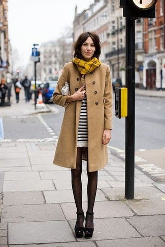 Go for a khaki coat and a white and black striped sweater dress to achieve a chic look. Round off this look with black suede heeled sandals.